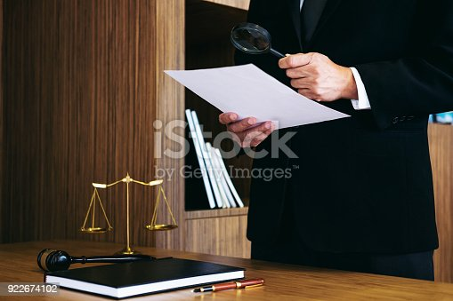 istock Male lawyer reading legal contract agreement and examining documents with magnifying glass in courtroom 922674102