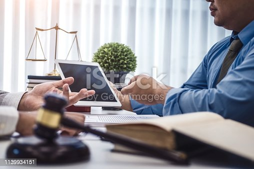 istock Male lawyer show tablet for explain a contract agreement to client for law .Law and Legal services concept. 1139934151
