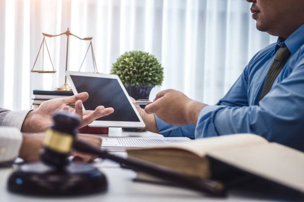 Male lawyer show tablet for explain a contract agreement to client for law .Law and Legal services concept. stock photo