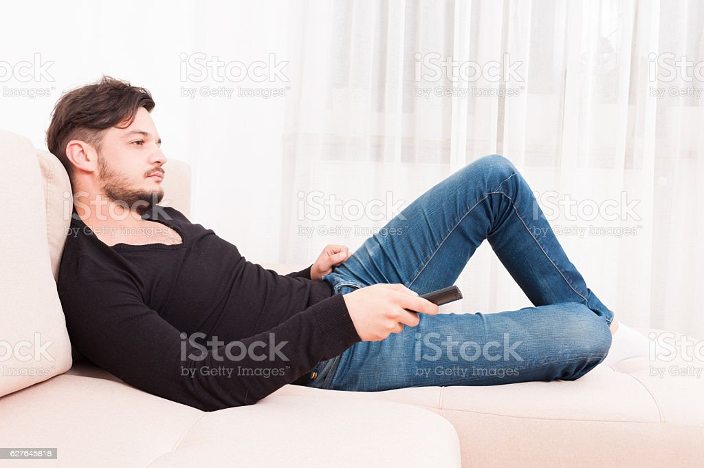 Male laying on sofa holding remote control stock photo