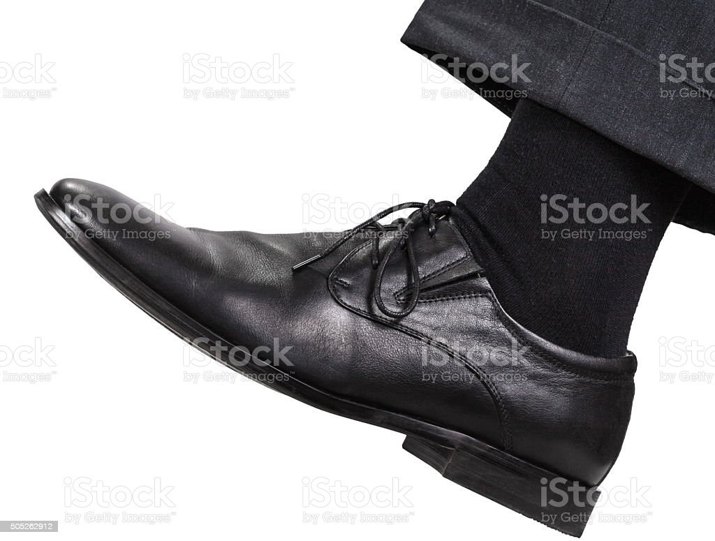male left leg in black shoe takes a step stock photo