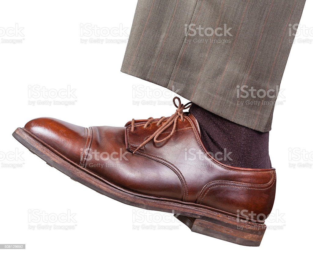 male left leg in brown shoe takes a step stock photo