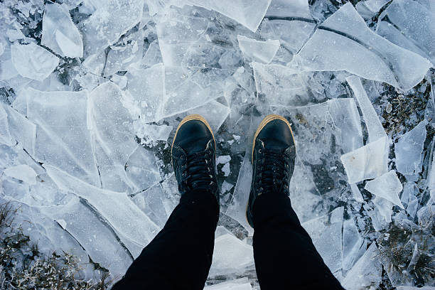 Male legs in leather boots standing on cracked ice – Foto