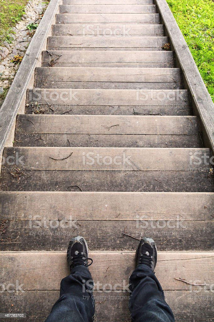 Male legs stand on old wooden stairs stock photo