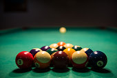 Male lines up billiard shot to sink a ball by the corner pocket