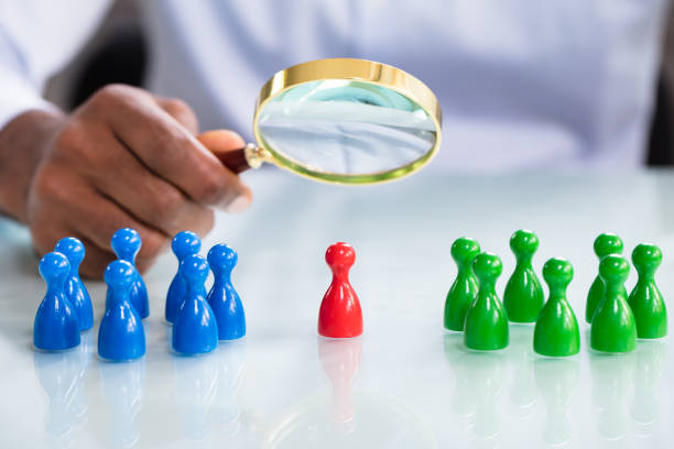 Male Looking At Colorful Pawns With Magnifying Glass stock photo