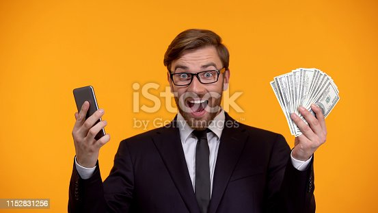 istock Male looking at smartphone and immediately receiving money cash back application 1152831256