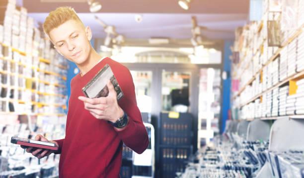männlich sucht cd und dvd im shop aufmerksam lesen - cd ständer stock-fotos und bilder
