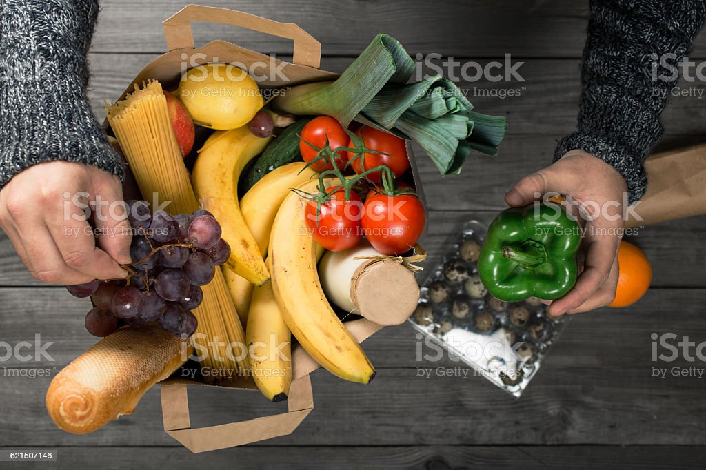 Male looks bag full of food on wooden table photo libre de droits