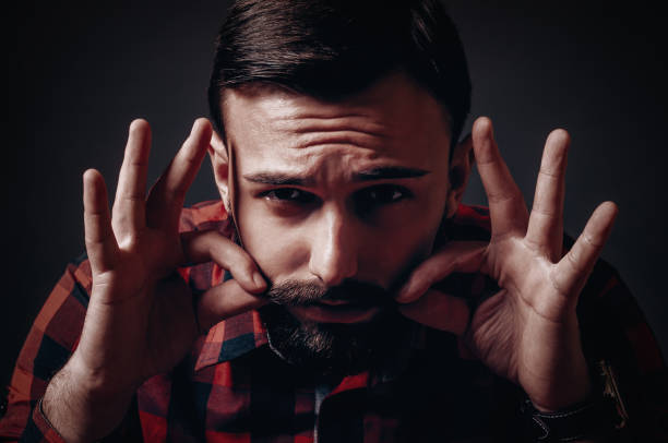 Male lumber jack model with beard twisting, pinching and waxing his mustache stock photo