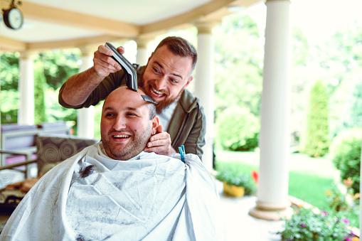 Männlich Machen Fehler Beim Trimmen Von Haaren Von Lächelnden Freund Zu Hause Stockfoto und mehr Bilder von Amateur