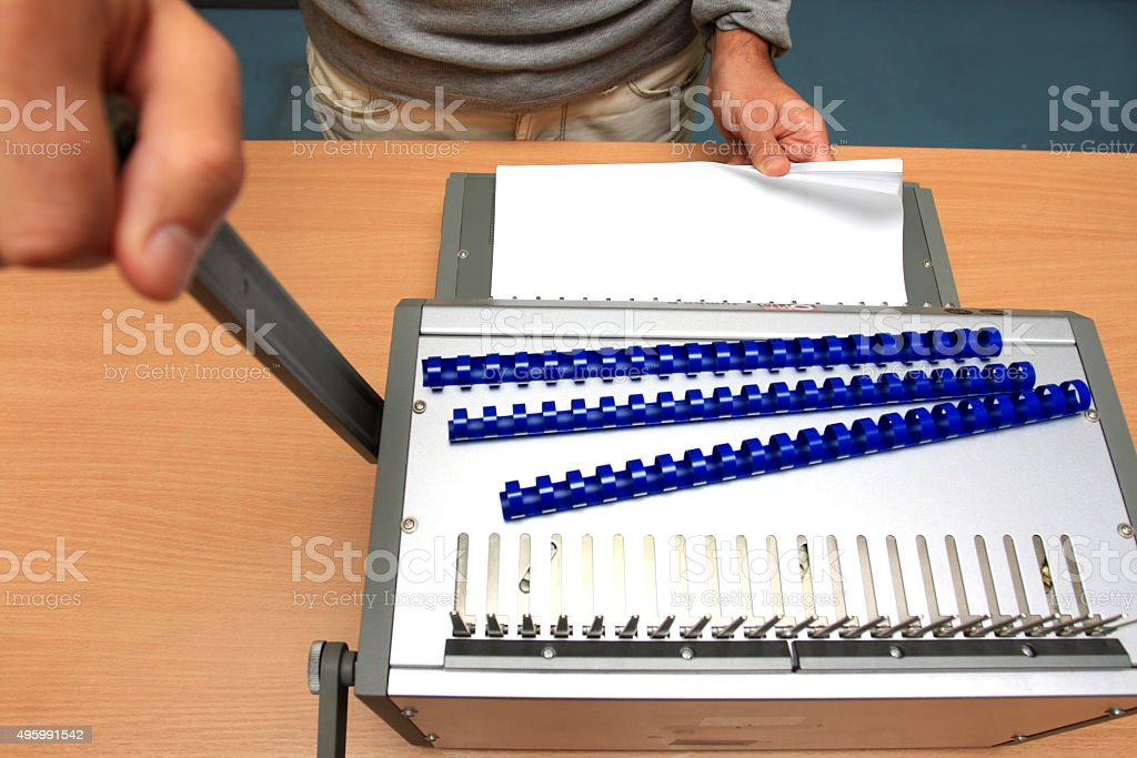 male man binding pages at table in paper store stock photo