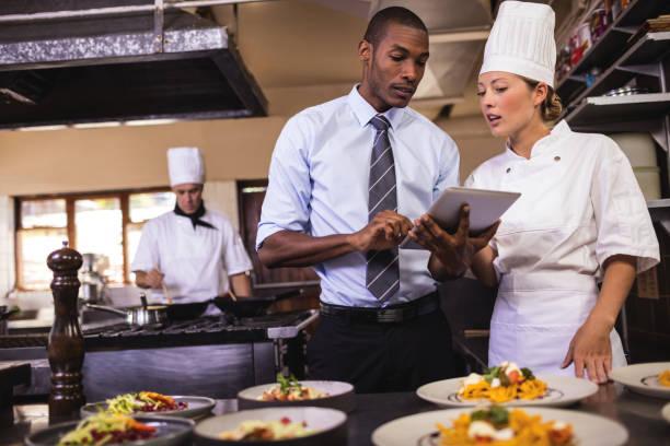 männliche manager und köchin mit digital-tablette in küche - leitende position stock-fotos und bilder