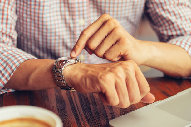 Male manager pointing at watch and sitting in cafe stock photo