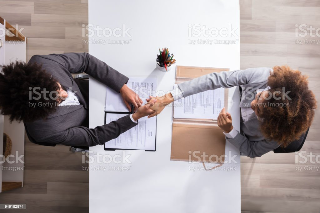 Male Manager Shaking Hands With Female Applicant stock photo