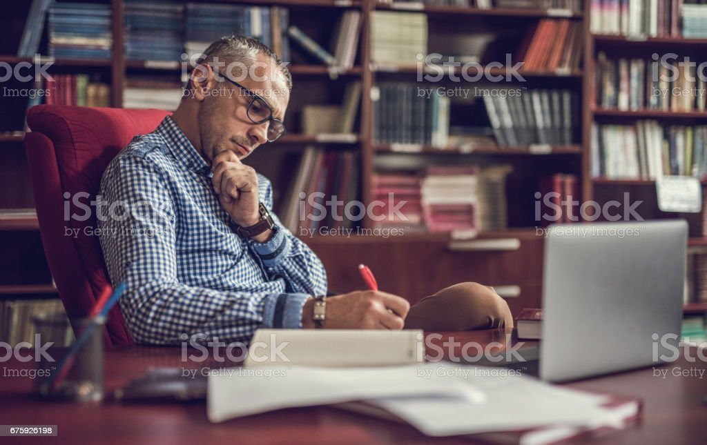 Male manager taking notes in home office.