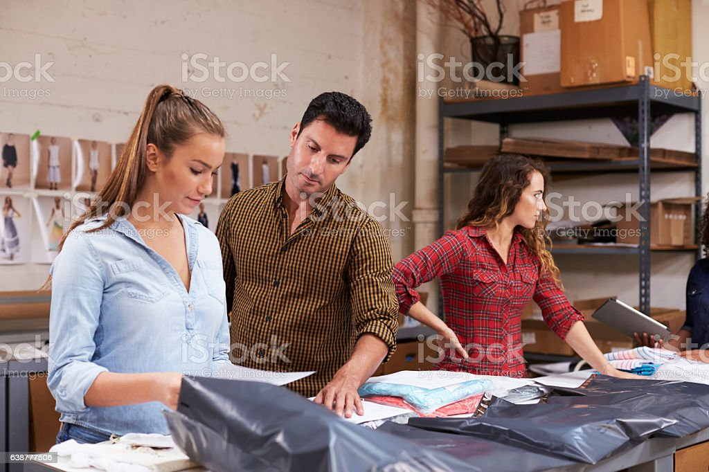 Male manager with trainee packing orders for distribution stock photo