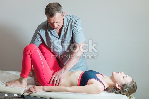 istock Male manual visceral therapist masseur treats a young female patient. 1161161072