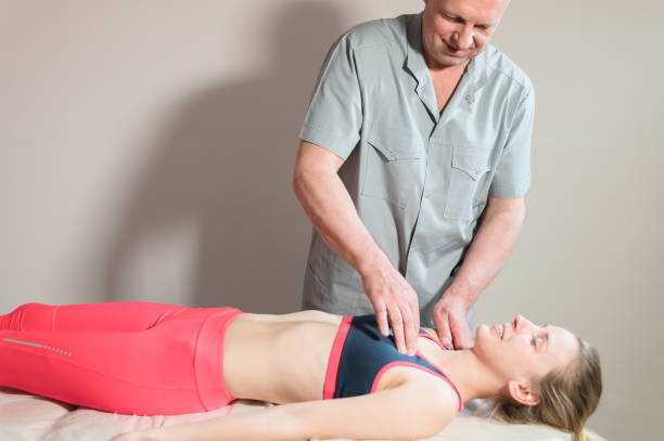 Male manual visceral therapist masseur treats a young female patient. stock photo