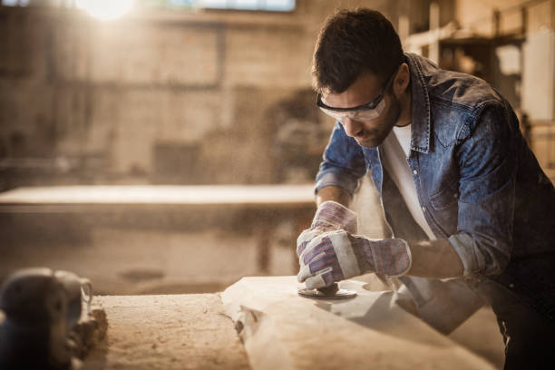 Male manual worker using plane while working on a wood in a workshop. stock photo