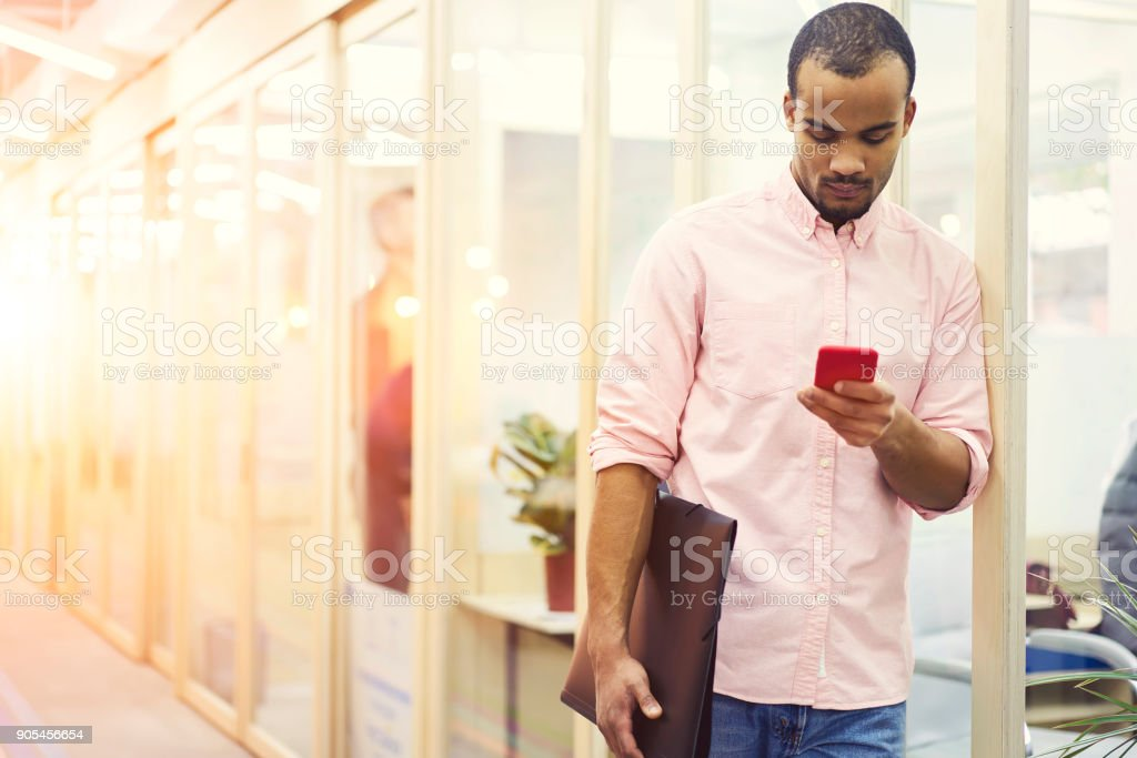 Male marketing expert uploading advertising content and multimedia files to webpage of company doing remote job while being on meeting using smartphone and wireless connection to internet indoor stock photo