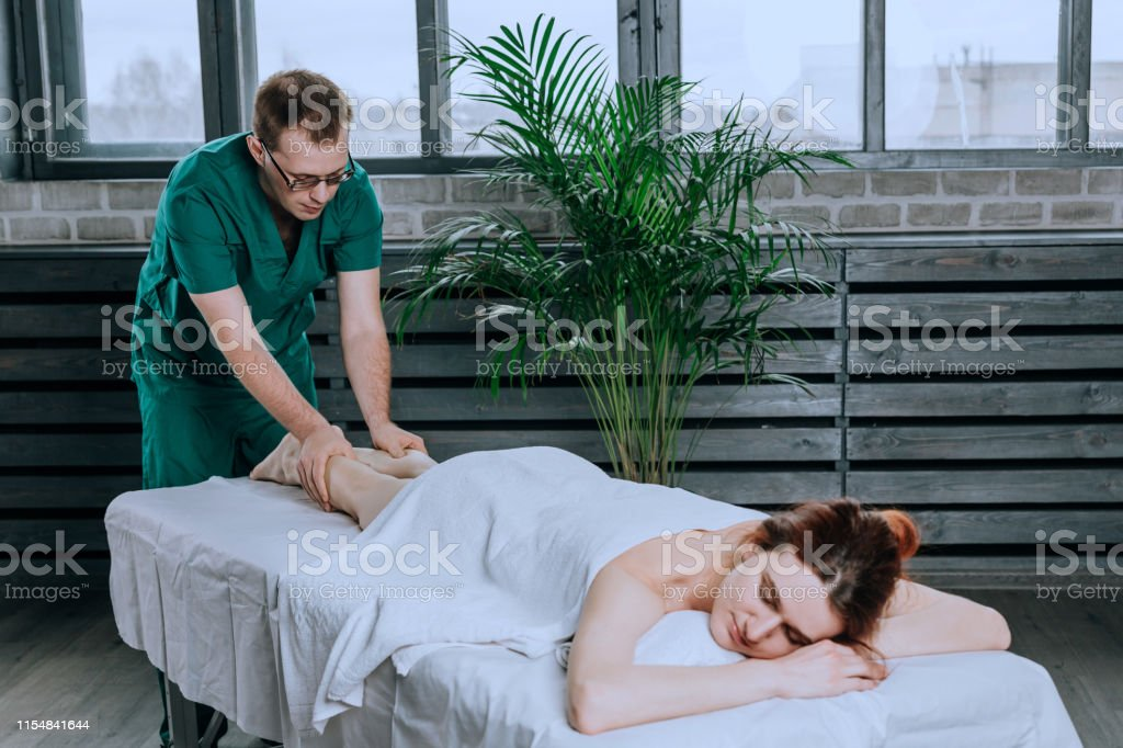 A male massage therapist massages the feet and legs of female legs.