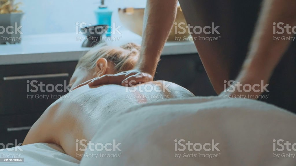 Male massagist massaging attractive lady's back. stock photo