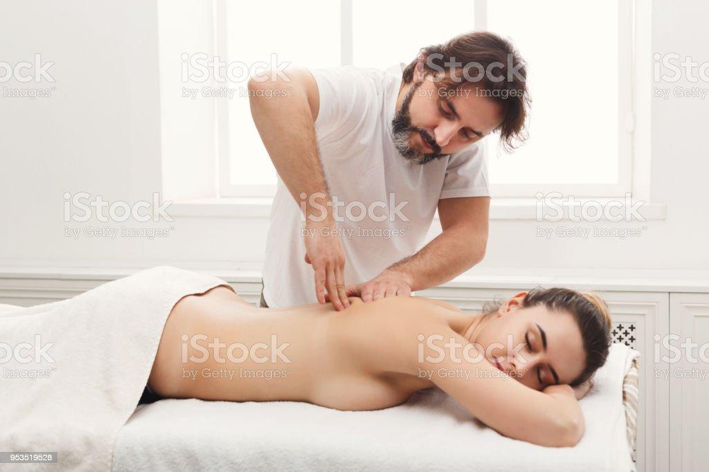 Male masseur massaging female back and shoulders. Professional body...