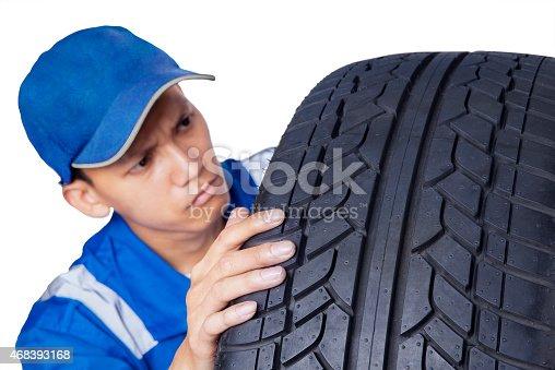 1047558948 istock photo Male mechanic checking a tire 468393168