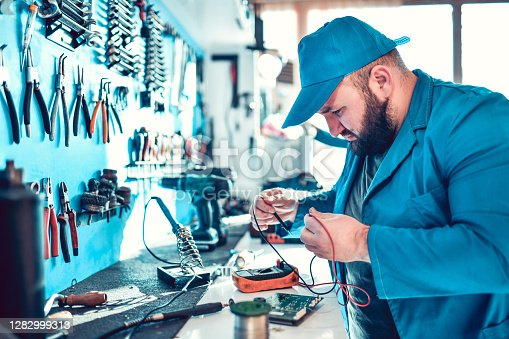 Male Mechanic Checking Impedance Of Electronic Device