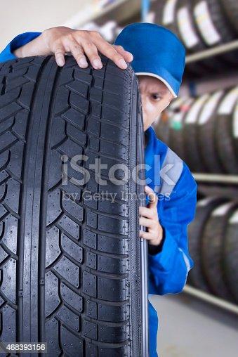 1047558948 istock photo Male mechanic checks a tire seriously 468393156