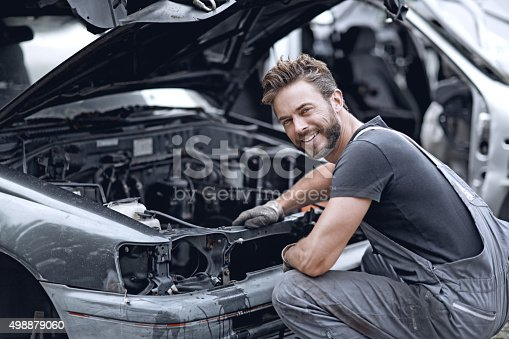 498879174 istock photo Male mechanic fixing car 498879060