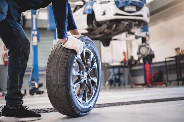 Male mechanic hold and rolling tire at repairing service garage background. Technician man replacing winter and summer tyre for safety road trip. Transportation and automotive maintenance concept Male mechanic hold and rolling tire at repairing service garage background. Technician man replacing winter and summer tyre for safety road trip. Transportation and automotive maintenance concept replacement stock pictures, royalty-free photos & images