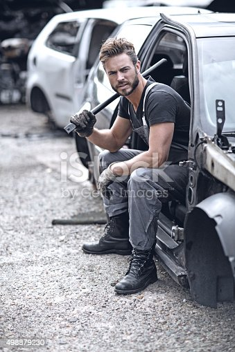 498879174 istock photo Male mechanic sitting in car at junkyard 498879230