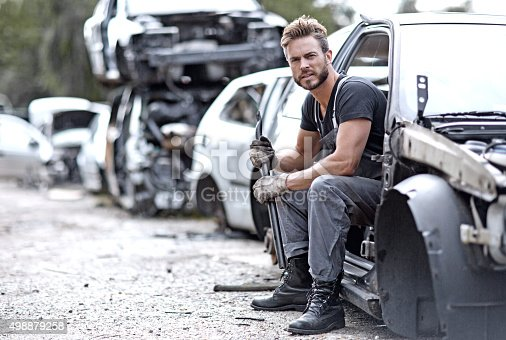 498879174 istock photo Male mechanic sitting in car at junkyard 498879258
