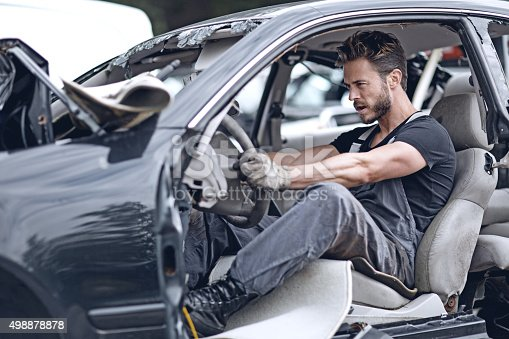 498879174 istock photo Male mechanic sitting inside broken car 498878878