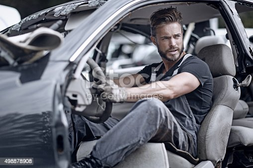 498879174 istock photo Male mechanic sitting inside broken car 498878908