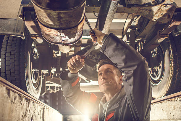 Male mechanic using socket wrench while working on chassis. stock photo