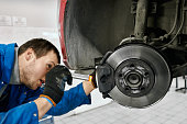 istock Male mechanic with open mouth wearing black gloves and blue uniform, holding flashlight and carefully examining tyres or brake pads of lifted car at auto workshop.Car service and technician concept 1152779095