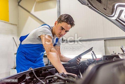 istock Male mechanic working in car service 1154970833