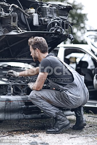 498879174 istock photo Male mechanic working on destroyed car 498879088