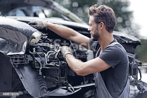 498879174 istock photo Male mechanic working on destroyed car 498879174
