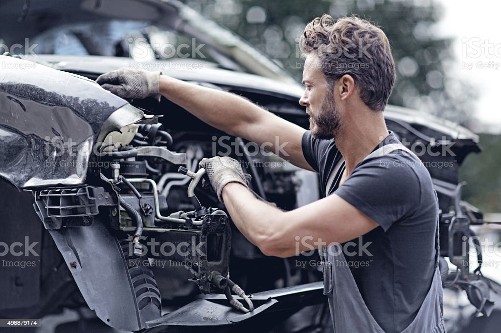Male mechanic working on destroyed car stock photo