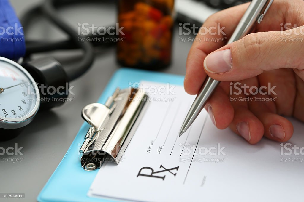Male medicine doctor hand write prescription to patient stock photo