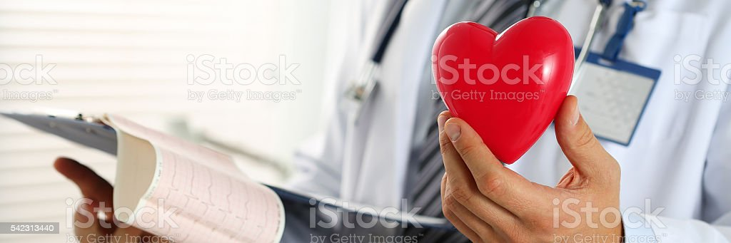 Male medicine doctor hands hold red toy heart and cardiogram stock photo