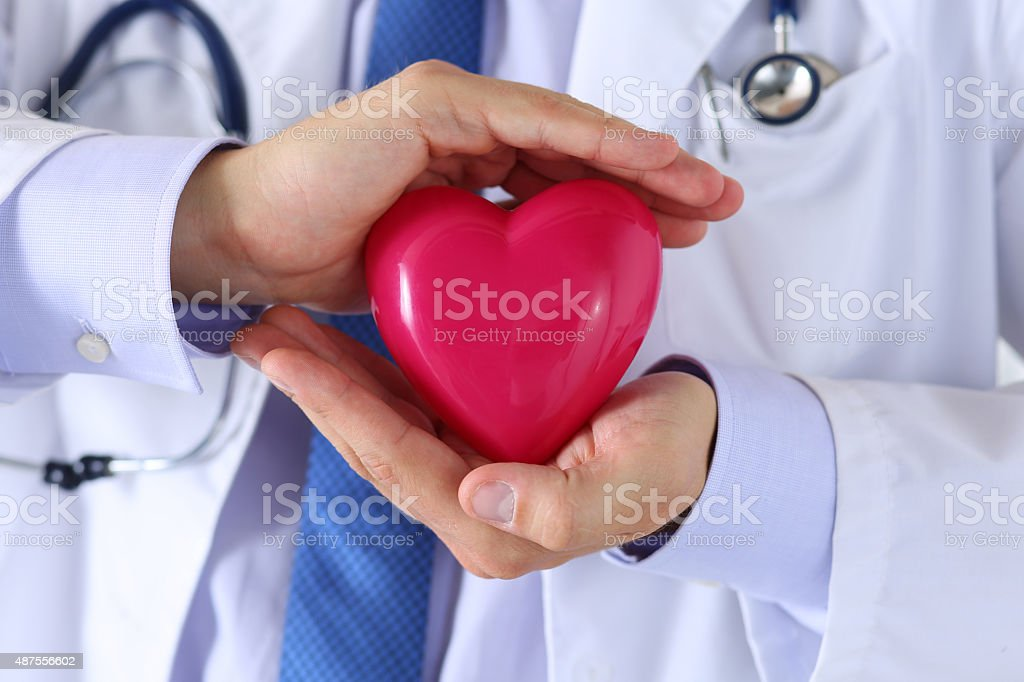Male medicine doctor hands holding and covering red toy heart stock photo