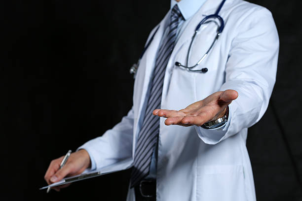 male medicine doctor offering helping hand closeup - money black background stock photos and pictures