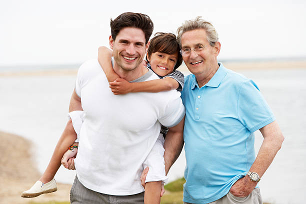 Male Members Of Multi Generation Family Standing By Sea stock photo