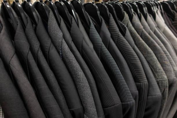 Hombres hombres trajes de negocios grises en perchas en una tienda, armario o barandilla de armario - foto de stock