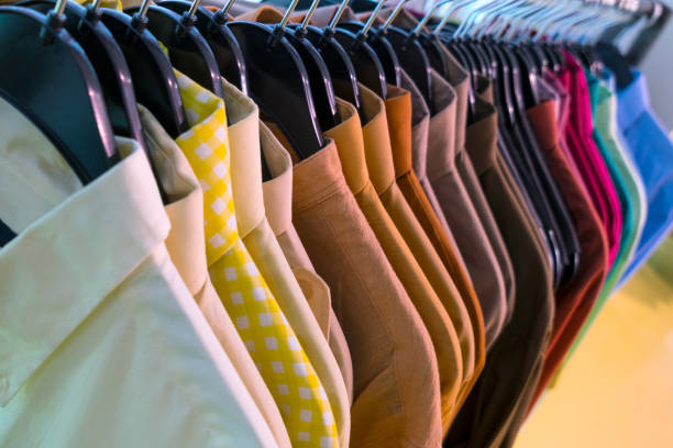 männliche menshemden auf kleiderbügeln auf einer shop-schiene - bügelsysteme stock-fotos und bilder